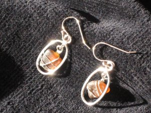 Sea glass nuggets, wire wrapped, in sterling silver hoops with shepherd hook earrings.