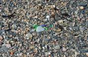 Naturally polished sea glass washes up on the beach