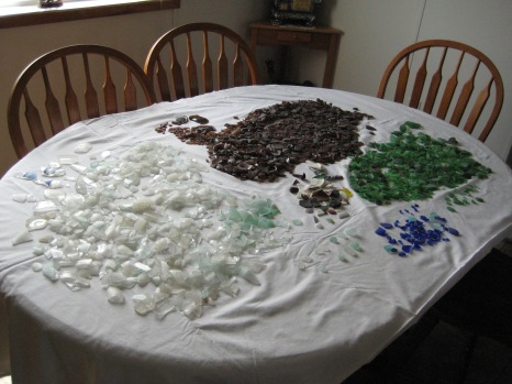 Glass being sorted by colour, and then shape and size.